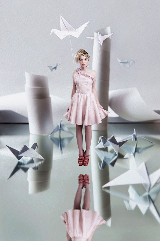 Conceptual fine art photography image of blonde girl in pink dress floating in origami paper world in conceptual portraiture by Johannesburg photographer Natalie Field