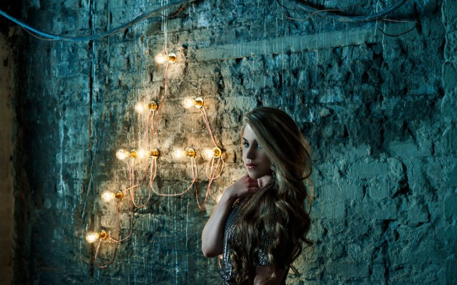 Portrait of Ashlinn Gray singer songwriter in bokeh light of bare bulbs