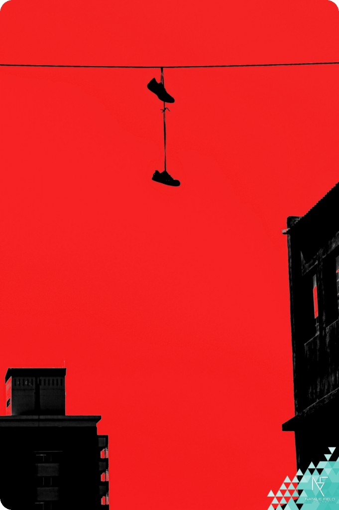 Shoes on a wire Johannesburg CBD inner city with red colour blocking by Natalie Field Photography