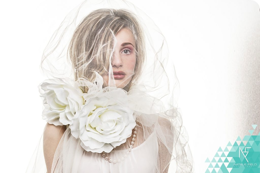 High key white-on-white photography of ethereal girl with veil and white flowers by Natalie Field Photography.