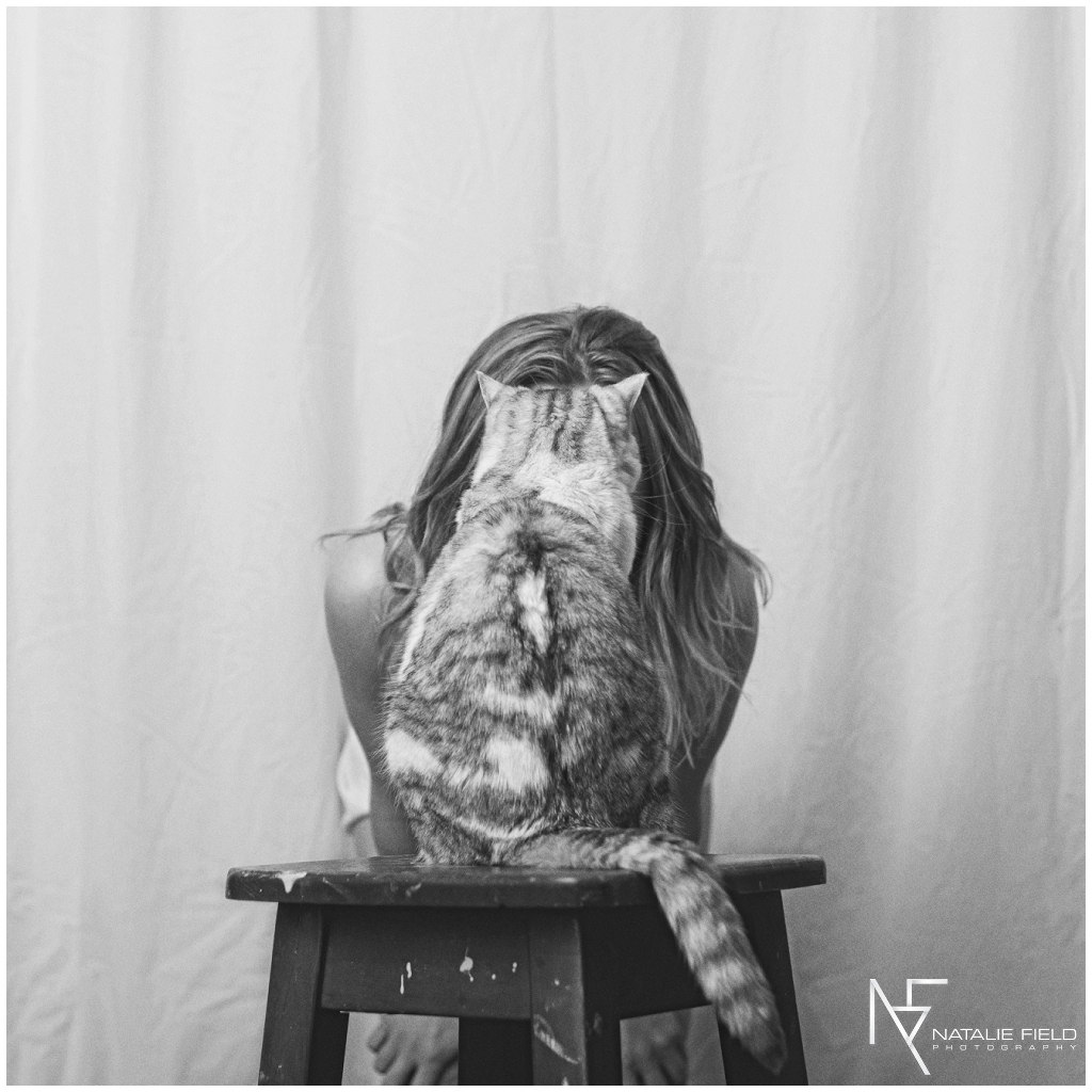 Fine art portrait of yogi behind cat on chair in black and white by Natalie Field Photography