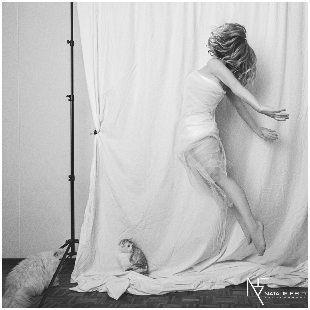 Fine art portrait of yogi jumping with cats watching in studio in black and white by Natalie Field Photography