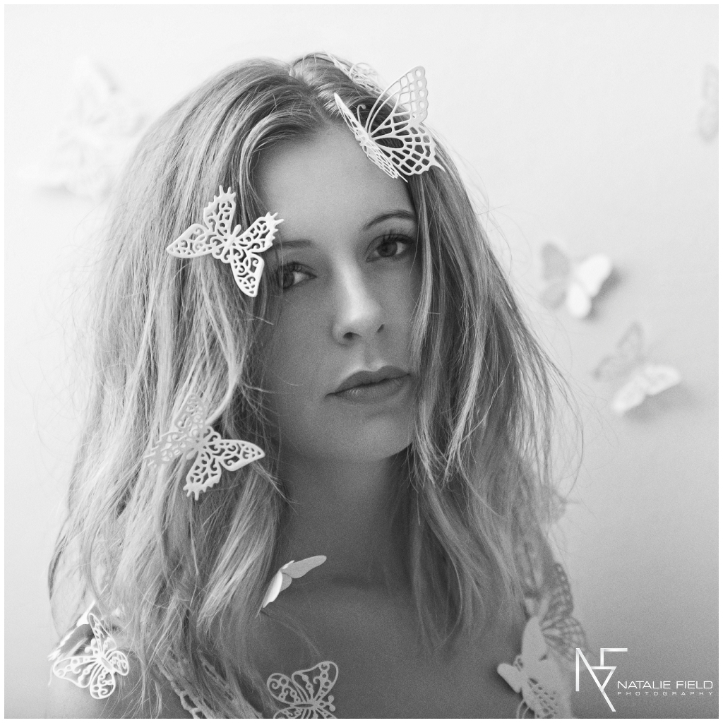 Fine art portrait of yogi Sarah Swoon wearing wedding dress covered with paper butterflies in studio in black and white by Natalie Field Photography
