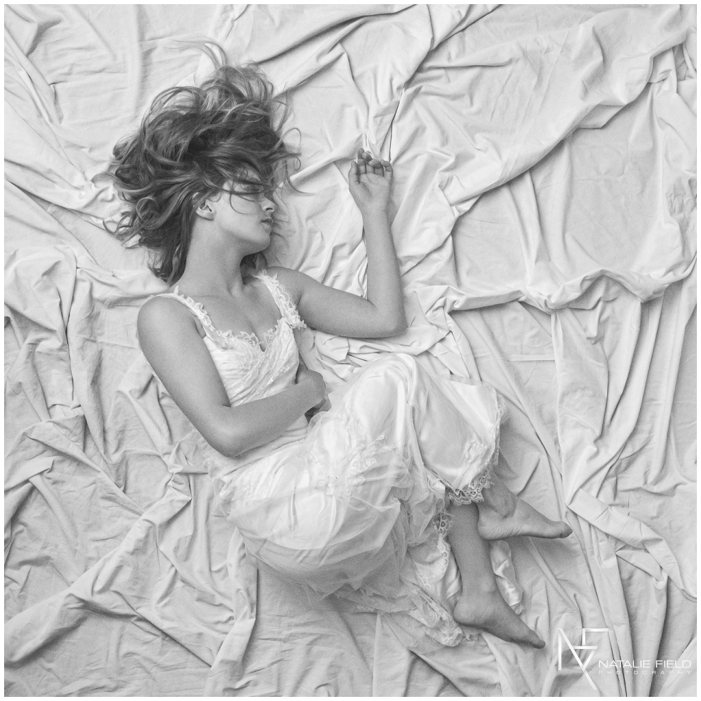 Fine art portrait of yogi in fetus position wearing wedding dress in studio in black and white by Natalie Field Photography