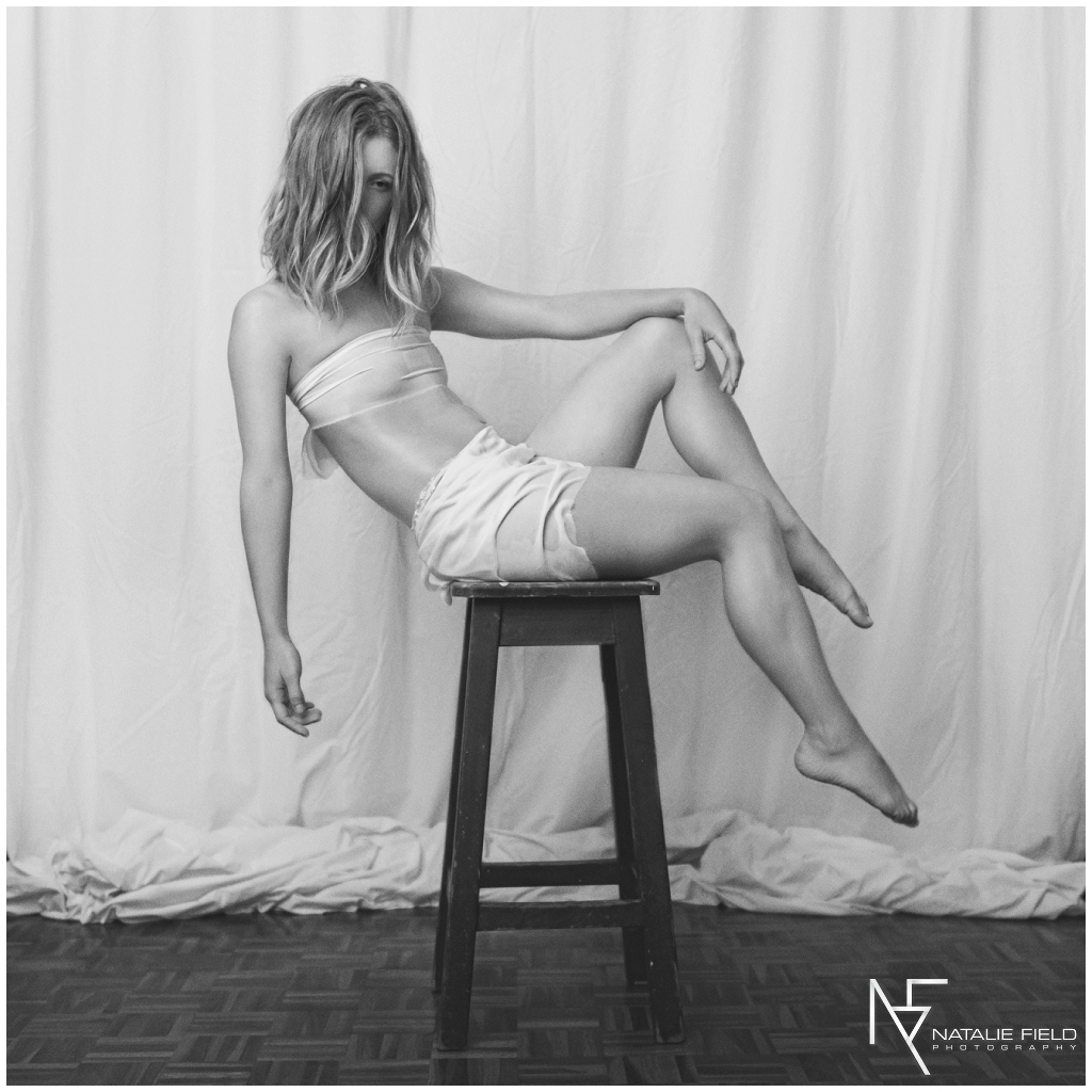 Fine art portrait of yogi behind on chair in studio in black and white by Natalie Field Photography