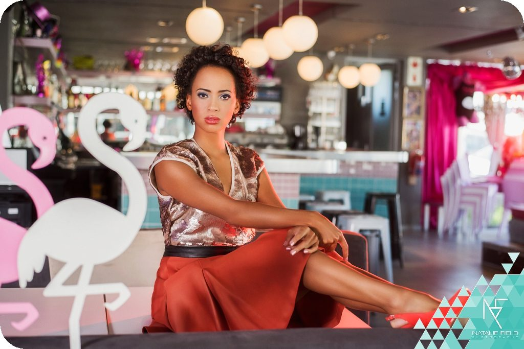 Retro Night fashion editorial features exotic beauty Tessa Lethoko in party scene with flamingos and pineapples at Beefcakes restaurant, dressed in bespoke fashion brand Clad Chic, photography by Natalie Field.
